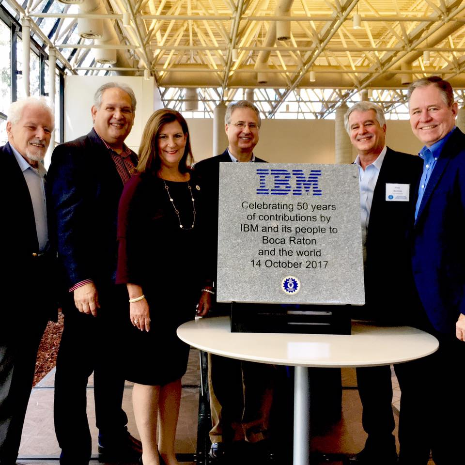 Group of business people standing behind an IBM placard